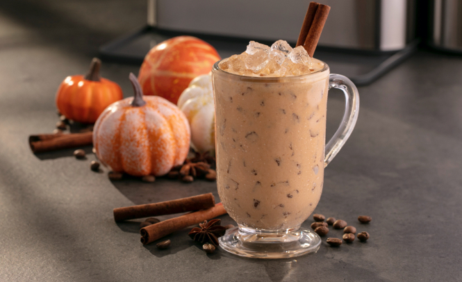An iced coffee drink sitting in front of miniature pumpkins