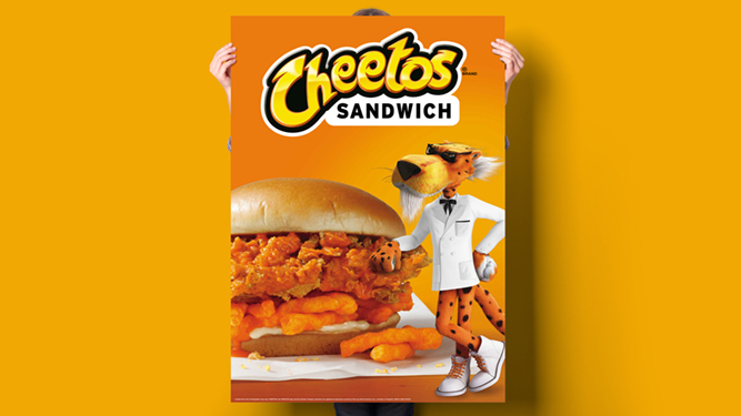 Person holding a posted with the Cheetos mascot standing next to a chicken and Cheetos sandwich