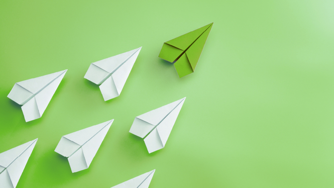 White paper airplanes following behind a green on