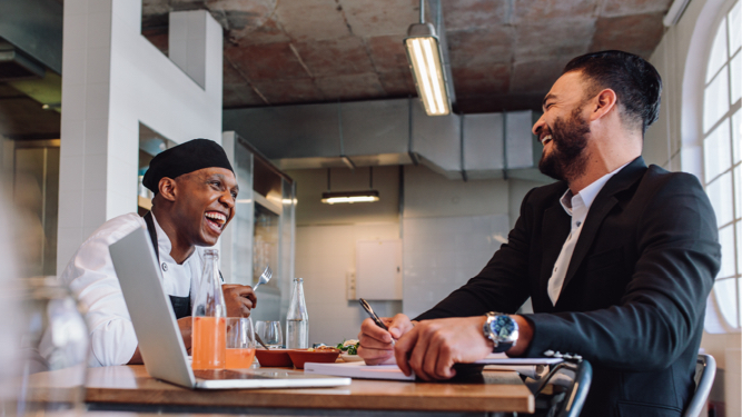 A business man and a chef sitting at a table and lauging