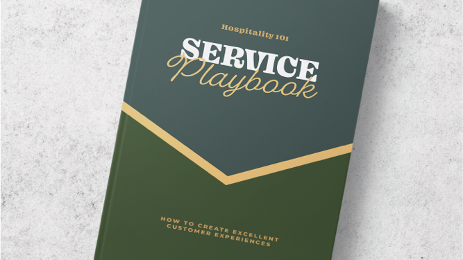 A green book sitting on a marble table with the words Service Playbook on the cover