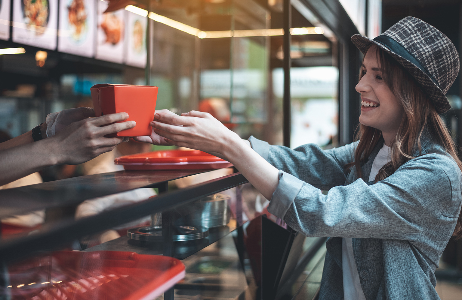 Woman receiving a to-go box at the point of sale